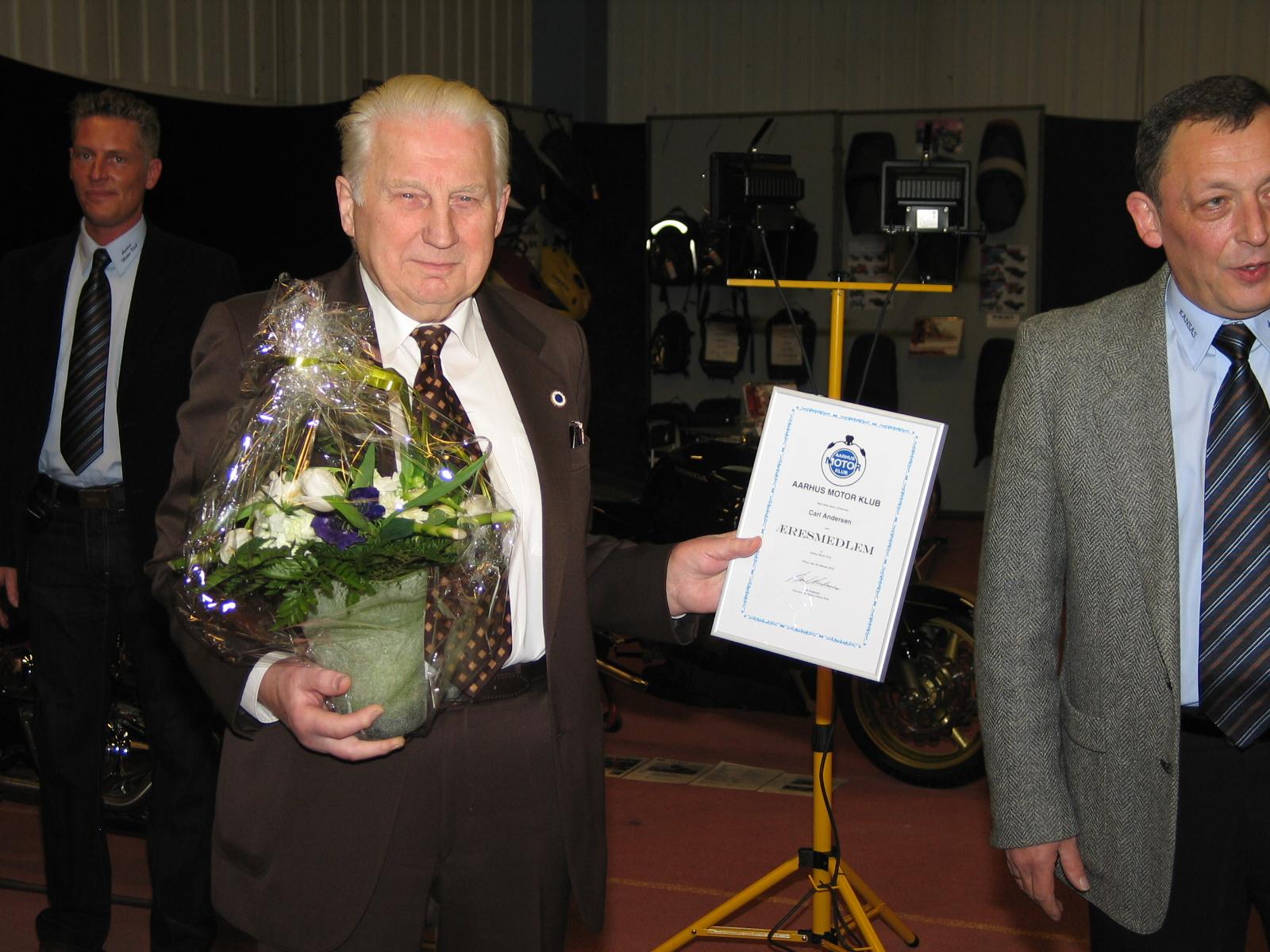 Carl modtager udnævnelsen som æresmedlem i AMK og får et diplom som bevis herpå.