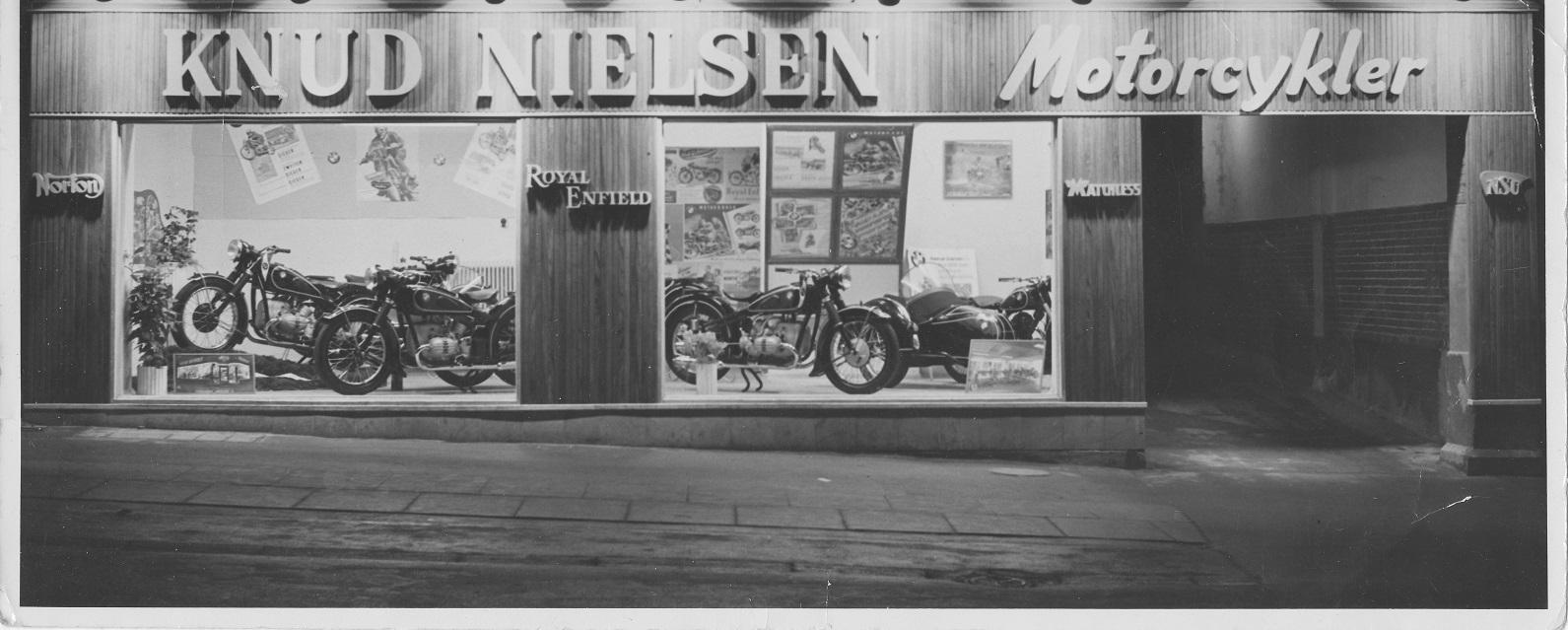 """Knud Nielsens forretning i Nørrebrogade. Billedet er fra de store mc-dage i 50´erne. Facadebeklædningen blev aldrig ændret, men """"Motorcykler"""" blev ændret til """"Automobiler"""", da tiderne skiftede."""