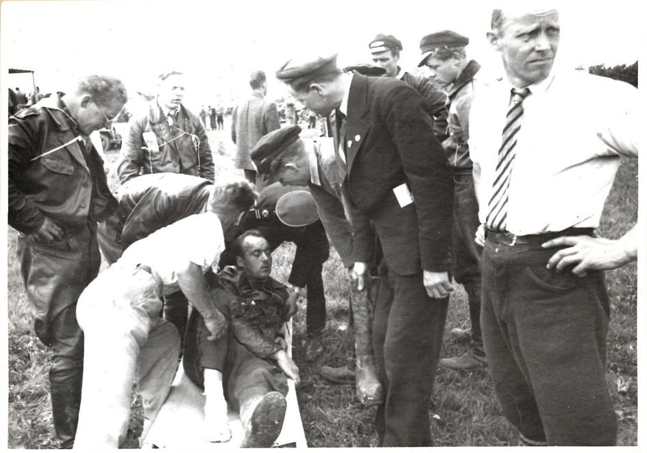 Uheldet ramte Knud ved et moto-cross stævne i Esbjerg 1. juni 1952, hvor han brækkede et ben. Knud ligger på båren, mens helt tv Carlo Sejer kikker til.