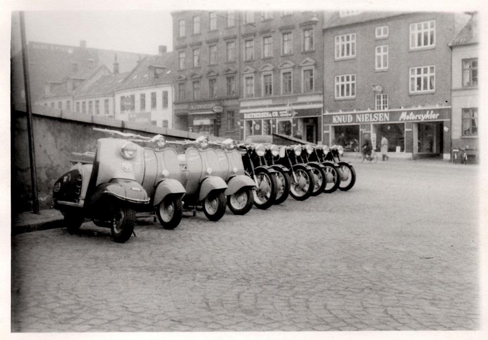 Inden de senere vejudvidelser lå Sabroes Plads overfor Knuds forretning. Pladsen blev kaldt Knud Nielsens plads i motorkredse. Her er det et parti TWN og Diana scootere sammen med en flok BMW klar til indregistrering og levering.