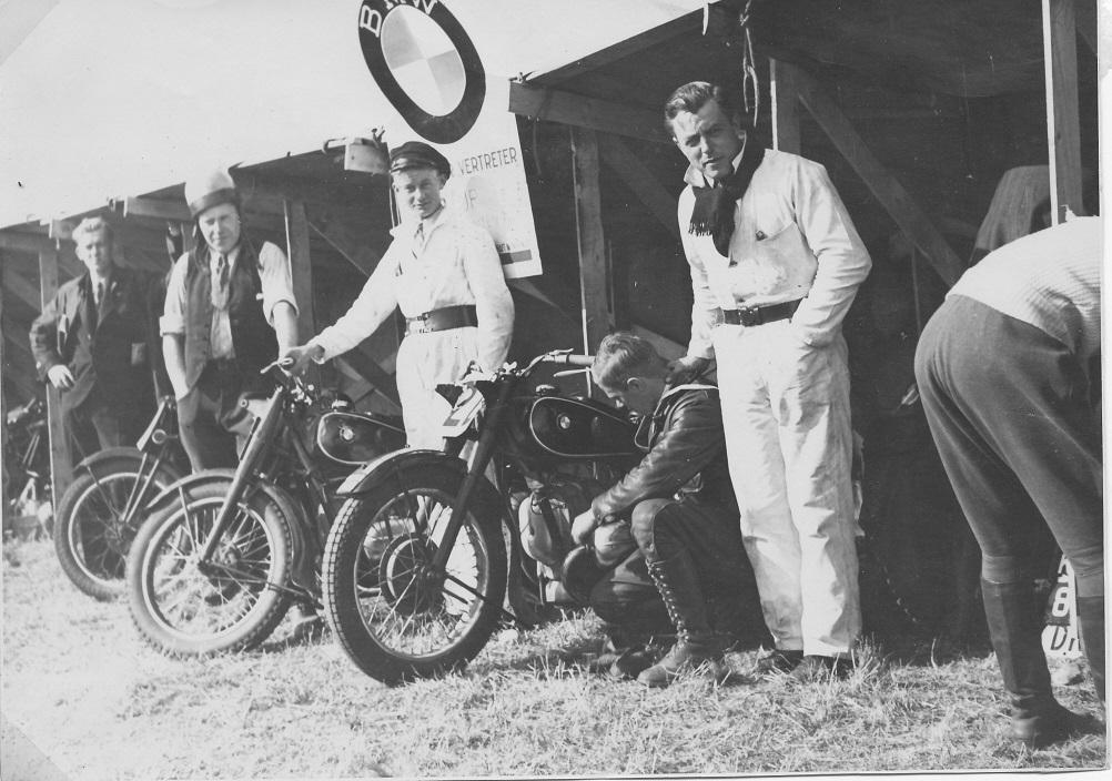 BMW holdet. Nr. 2 fra venstre er Carlo. Mekanikeren i den hvide kedeldragt th er Frank Nielsen, et markant klubmedlem. Knælende ved siden af Frank er det Robert Berke Jørgensen, mangeårig kasserer i klubben, som blev nr. 4 i løbet efter Carlo.