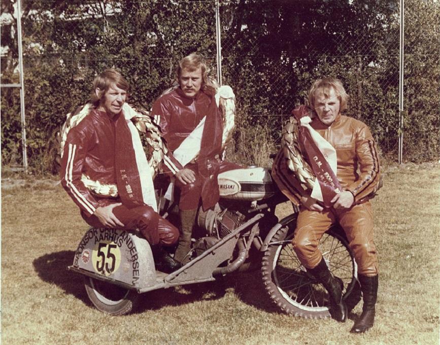 Ved DM i Ålborg i 1973 blev der to titler til Kawasaki. Carsten Jørgensen til højre vandt igen i 250cc, mens Finn Møller til venstre og John Steffensen vandt sidevognsklassen til 750cc. Billedet er taget i tiden efter løbet på firmaadressen på Randersvej. Derfor de fine rene dragter, der nok lige er lånt på lageret.