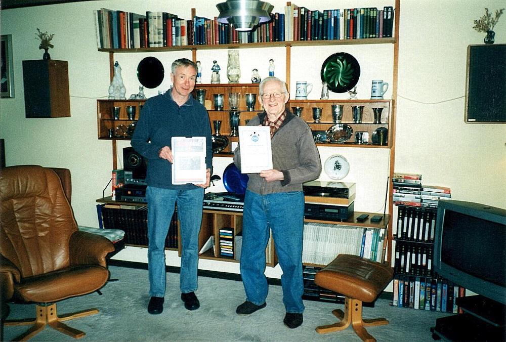 Aksel blev udnævnt til Æresmedlem i AMK 2006. John Williams og Lars Pedersen overbragte beviset i Aksels hjem i Skanderborg. Her Lars Pedersen og Aksel.