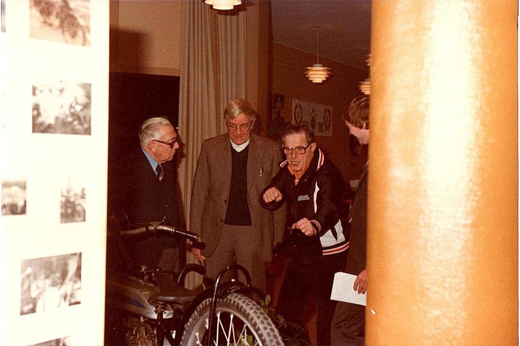 """AMK´s 50 års Jubilæumsreception på Varna 1980. Aksel fortæller levende om, hvordan den udstillede Douglas 1930 skal køres. Til venstre """"Murerras"""" og Henning Pedersen. Til højre Lars Pedersen."""