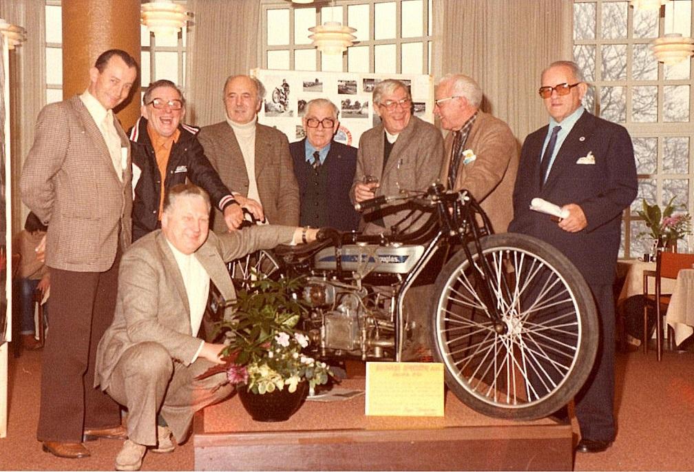 AMK´s 50 års Jubilæumsreception på Varna i 1980. Medlemmer med over 25 års medlemskab blev samlet om den udstillede Douglas Racer. Fra venstre er det Preben Woer, Aksel, Knud Nielsen, Murerras, Henning Pedersen, Carlo Sejer, Povl Serena og Carl Andersen siddende.