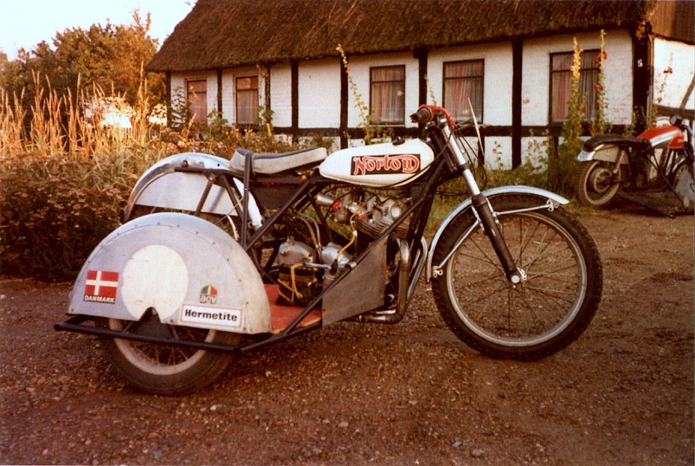 """Det var denne sidevognscykel, som """"Service"""" og Ole fik opbygget i vinteren 76/77. Motoren var en kortslaget Norton img1. I baggrunden Ole Møllers daværende hus i Haar, som senere blev overtaget af Svend Andersson."""