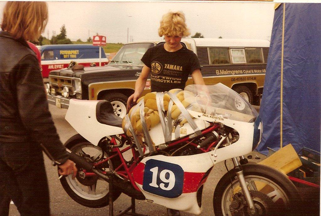 Karlskoga 1980. Paul brækkede et kraveben under træningen, så dette pudedyr blev konstrueret til aflastning i nedbremsningerne under løbet. Chris Jensen kikker på projektet.