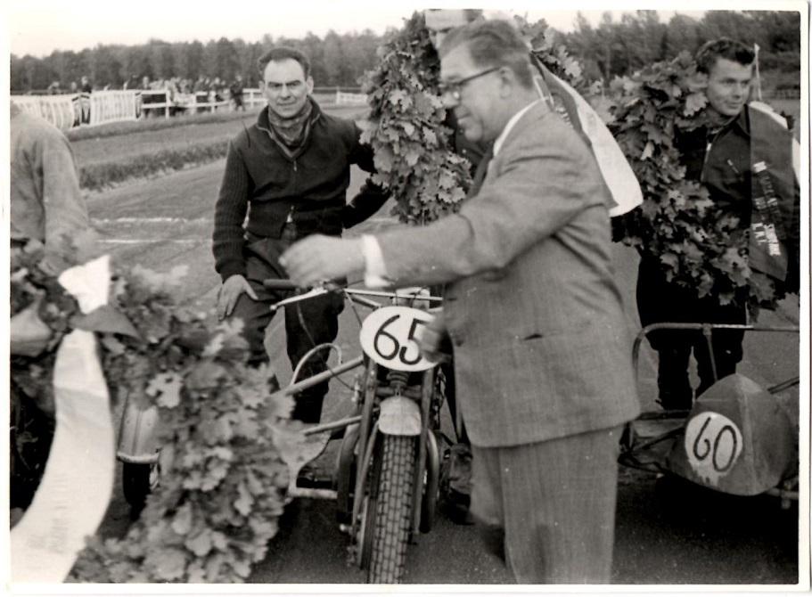 Holger som JMS formand uddeler laurbærkranse til Danmarksmestrene på Væddeløbsbanen 1957. Med nr. 65 er det Leo Peteren med John Østerholt i sidevognen.