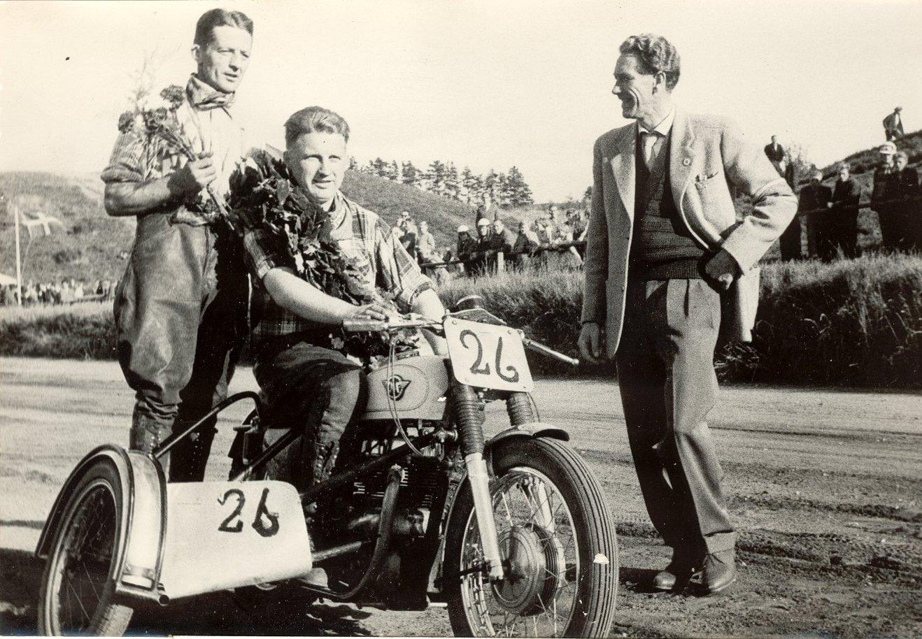 JM Løvel i 1959. Far var løbsleder, som det hed dengang og lykønsker her Carl Andersen og Gunnar Williams med titlen i 500cc sidevognsklassen.