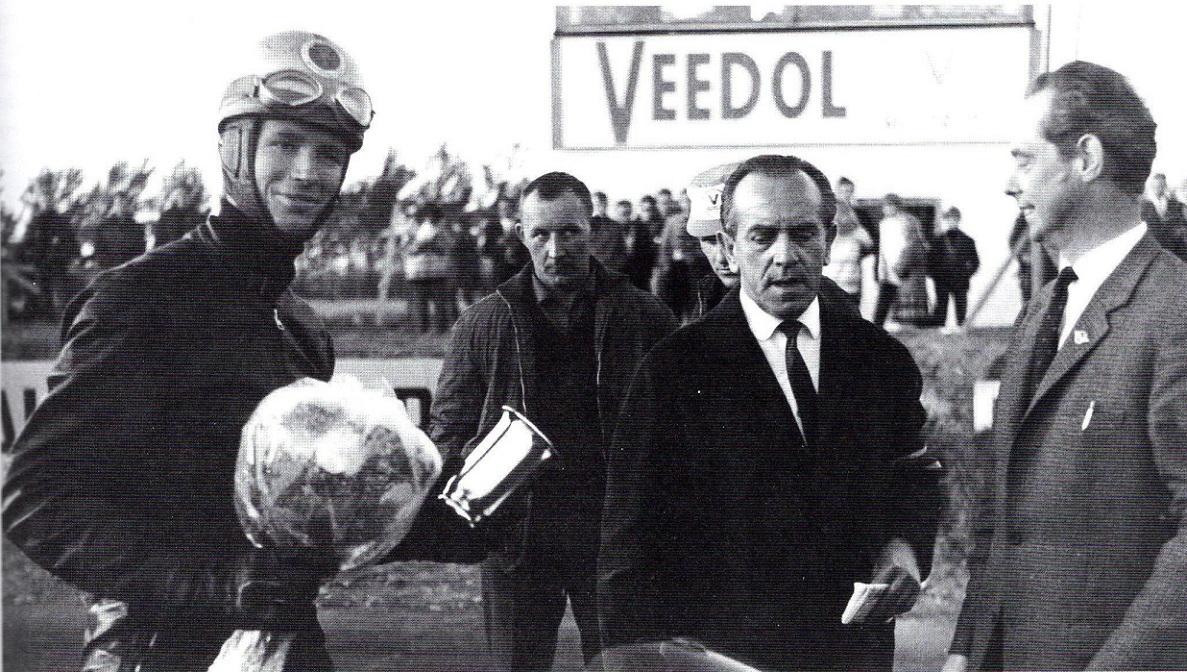 Kent Andersson har fået sin præmie, mens Jimmy Smed kikker i baggrunden. De to ledere fra Randers th er Svend Aage Rasmussen og Orla Jensen. (Alstrups bog)