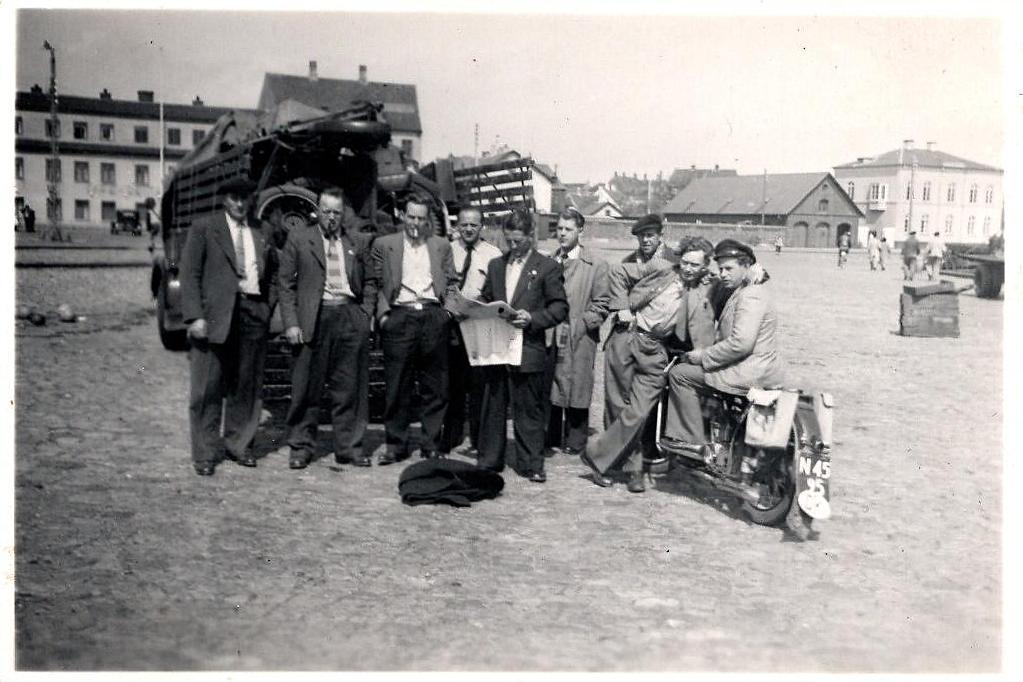 Fra turen i 1954. Gunnar Williams læser avis. Til hæjre for ham Kresten og Bakmand Skovsen. Motorcyklen th er nok fra Haderslev med N bogstavet fra Åbenrå Amt.