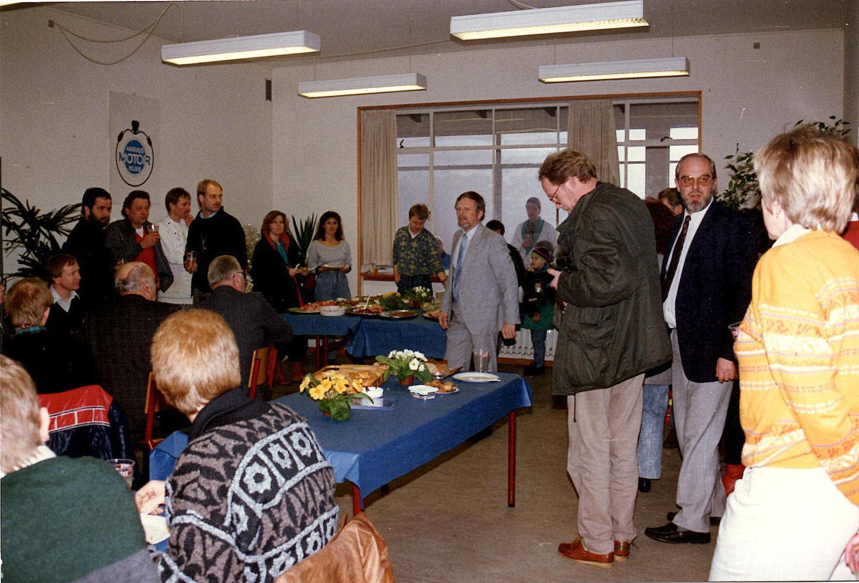 Erik Dam ses tv i hvidt kokketøj under AMK-logoet. Lejligheden er AMK´s 60 års Jubilæumsreception i 1990 på Søsporten, hvor Erik leverede maden.
