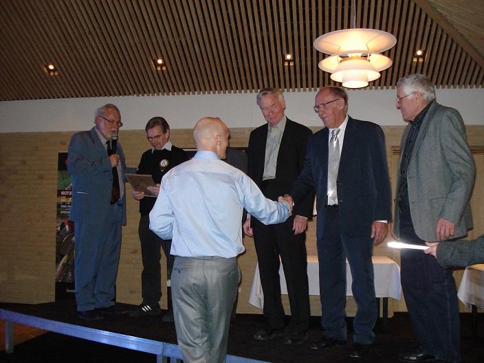 DMU´s generalforsamling marts 2011 i Horsens. 50 års jubilarer blev fejret og jeg var blandt de 5 det år. Per Østergård tv interviewer. Formand Jørgen Bitch gratulerer fra venstre Jens Bakmand Skovsen, Åge Nickelsen skjult bag Bitch, jeg selv, Arnold Nielsen og Ebbe Sørensen.