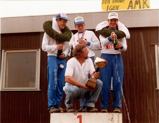 I et gyldent 10-år fra 1984 til 1993 vandt AMK 7 titler i DM for hold. Kernen på holdet var Kim Kjær, Povl Bovbjerg og Søren B. Mortensen, der her ses på skamlen efter mesterskabet i 1990 sammen med holdleder og klubformand Niels Laustsen.