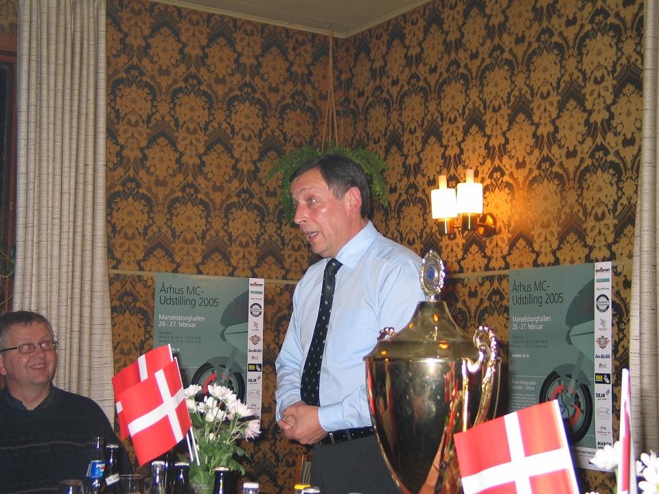 Formanden har ordet. Knud Møller tv. Plakater for Jubilæumsarrangementet i Marselisborg-hallen på væggene.