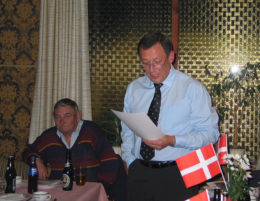 Generalforsamlingen 2005. Formand Bent Andersen taler, Service lytter. Service var typisk med som tilhører, indtil pligterne som krovært kaldte, når kaffen og rullemadderne skulle serveres.